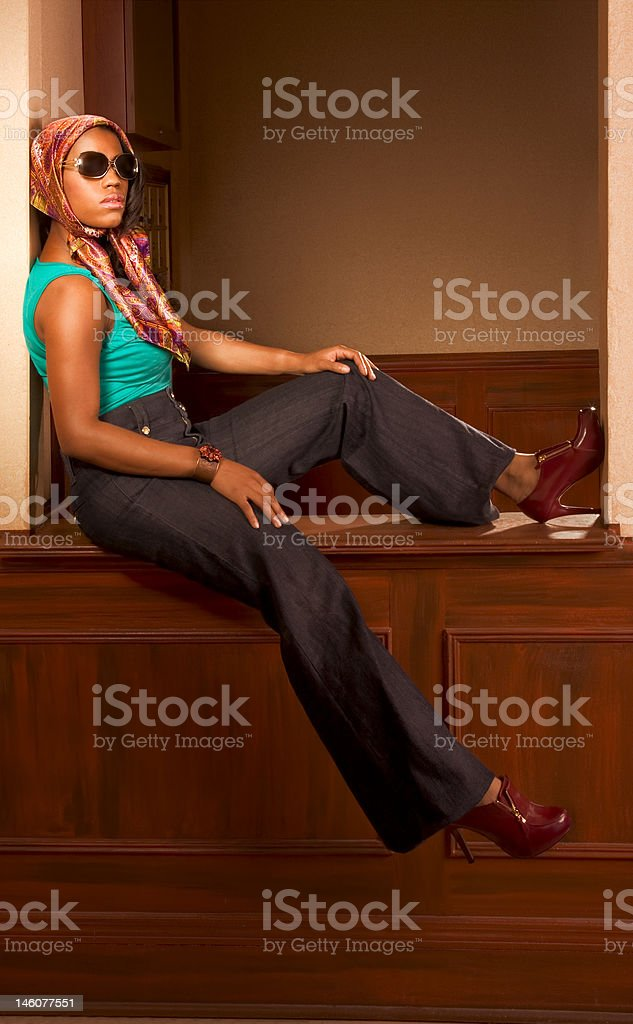 Urban African-American woman in jeans sitting on countertop royalty-free stock photo