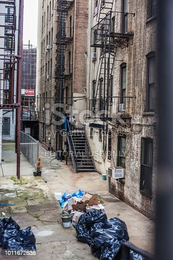 New York City, United States of America - July 29, 2018. An urban alleyway in Harlem is filled with bagged garbage.
