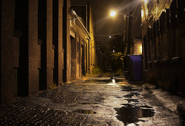 Urban Alleyway with Puddles at Night  alley stock pictures, royalty-free photos & images