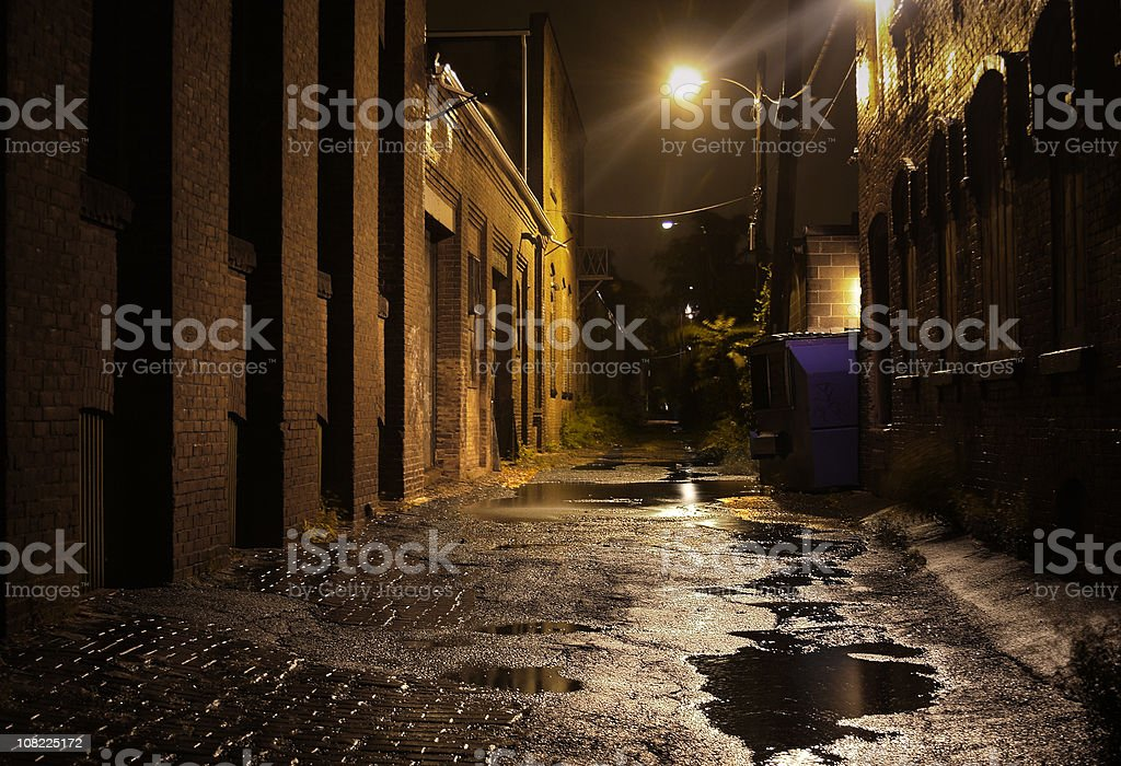 Urban Alleyway with Puddles at Night stock photo