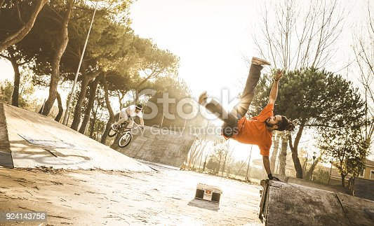Urban athlete breakdancer performing acrobatic jump flip at skate park - Guy riding bmx bicycle behind mate acrobat dancing with extreme move - Breakdance and friendship concept - Warm sunset filter