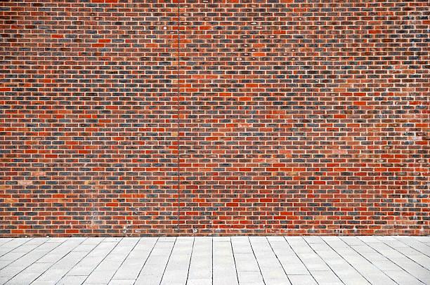 Urban background UK - Red brick wall with sidewalk stock photo