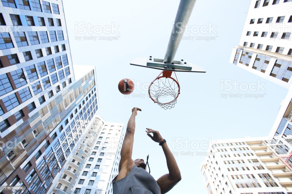 Low angle view at African basketball player shooting slam dunk...