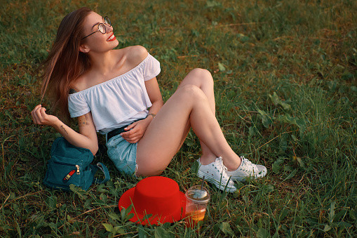 istock Urban beautiful girl taking a healthy break in the park resting on the grass 1010542648
