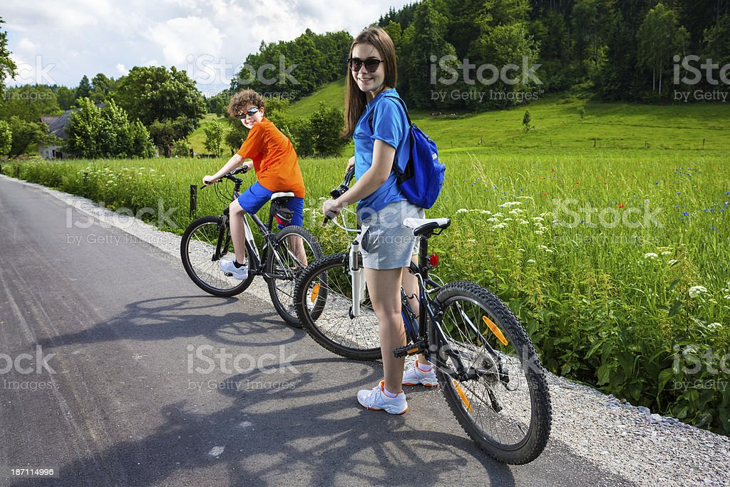 Urban biking- girl and boy riding bikes in city park royalty-free stock photo