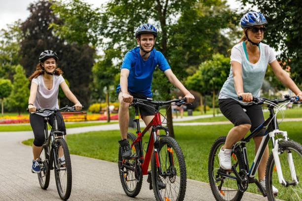 urban bike-drei personen reiten fahrräder in der stadt - fahrradwege stock-fotos und bilder