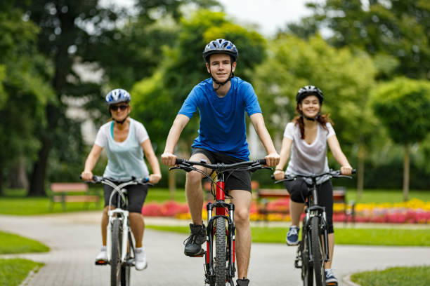 urban biking- three people riding bikes in city - cycling stock pictures, royalty-free photos & images
