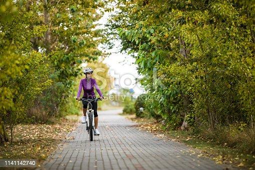 Urban biking - woman riding bike on cycle lane
