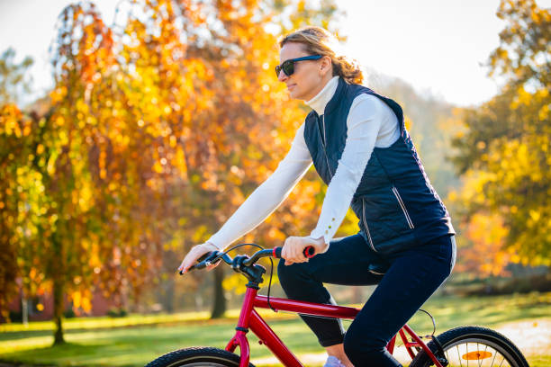 Urban biking - woman with bike in city park Urban biking - woman with bike in city park female biker resting stock pictures, royalty-free photos & images