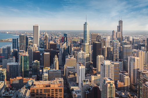 Aerial view of urban Chicago Cityscape under blue summer skyscape in warm golden hour light. Chicago, Illinois, USA