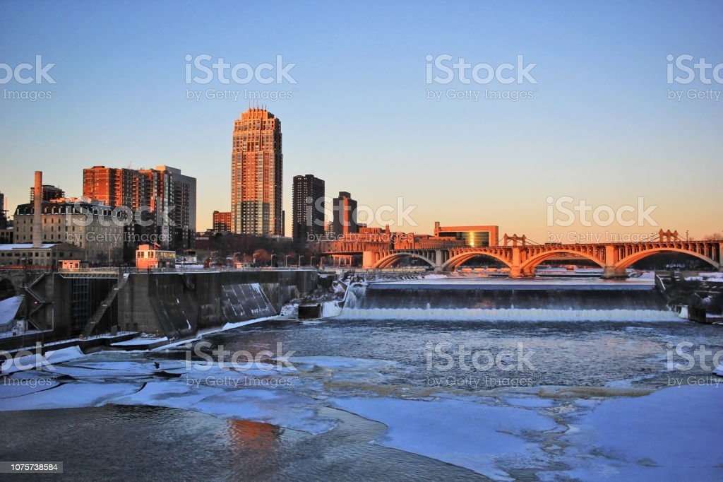 Urban city architecture background. Beautiful winter morning in Minneapolis. Downtown cityscape with Mississippi river, Third Avenue Bridge above Saint Anthony Falls and skyscrapers during sunrise. Minnesota, Midwest USA. Architecture Stock Photo