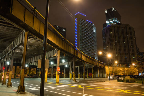 Urban city street corner with vintage train bridge and skyscrapers in Chicago at night stock photo