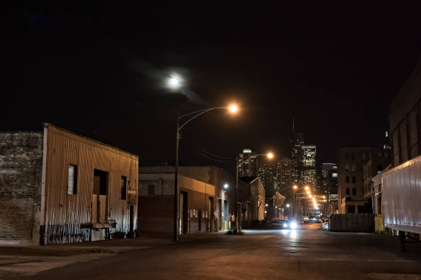 Urban city street with vintage industrial warehouses and the Chicago skyline with the moon at night stock photo
