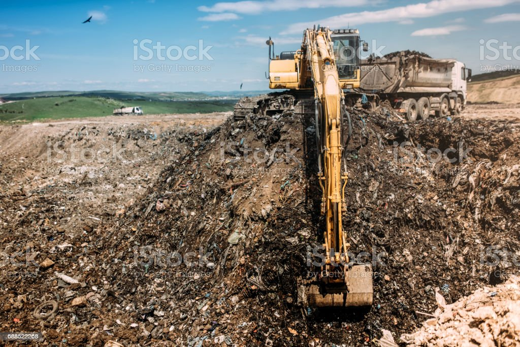 Urban city waste dumping grounds with excavator loading trucks stock photo