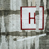 Urban concrete wall with painted letter H