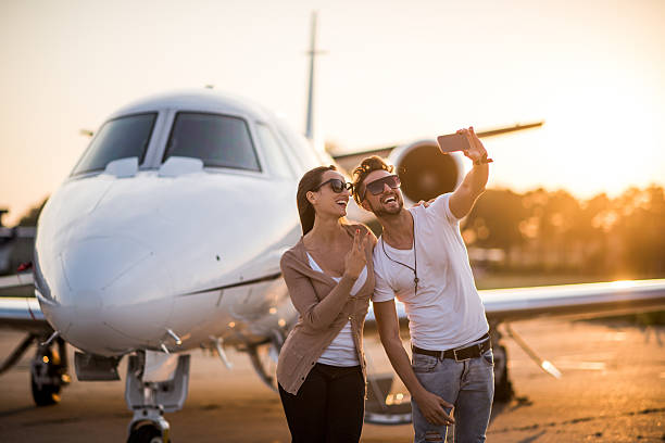 Urban couple making a selfie at the airport stock photo
