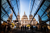 Color image depicting a crowd of people, thrown into silhouette and therefore unrecognisable, walking alongside modern futuristic architecture of glass and steel. In the distance we can see the ancient and iconic dome of St Paul's cathedral. Room for copy space.
