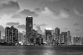 This is a horizontal, black and white photograph of United States travel destination, Miami, Florida viewed from Key Biscayne. Miami's changing cityscape skyline lights up at night. Buildings are brightly lit and reflect on the dark water's surface. Photographed with a Nikon D800 DSLR camera.