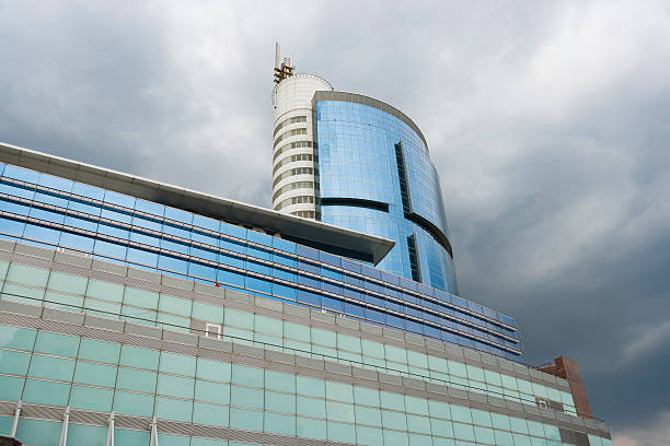 Urban Entreprise Modern office building under dark clouds. entreprise stock pictures, royalty-free photos & images