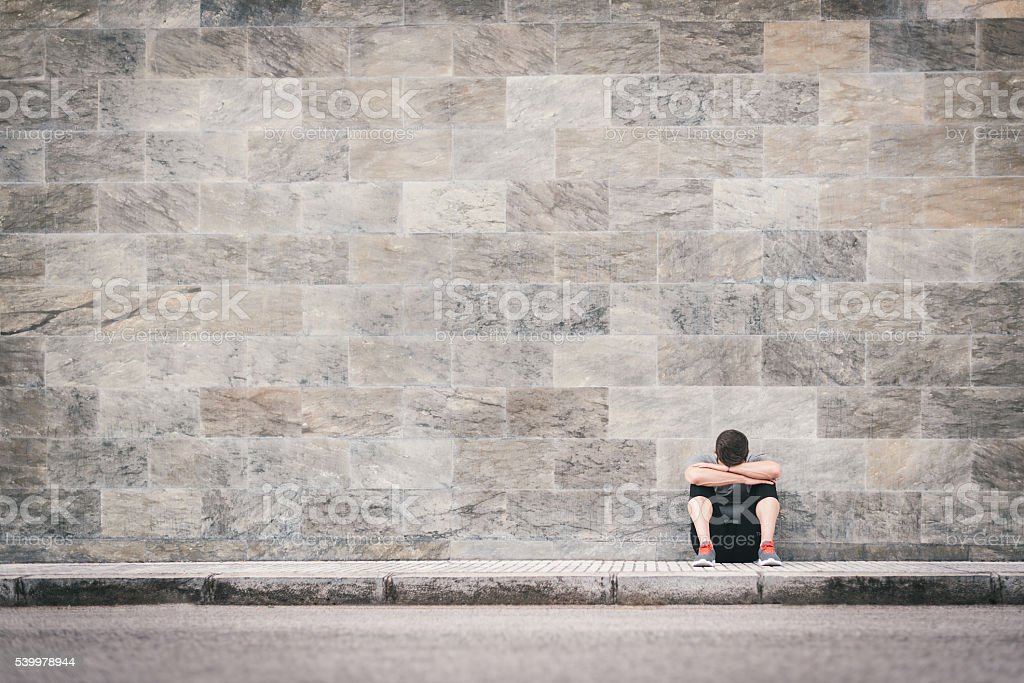 urban exhausted fitness man outdoor sitting on the floor stock photo