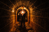 Urban explorer with candle in old vaulted underground tunnel