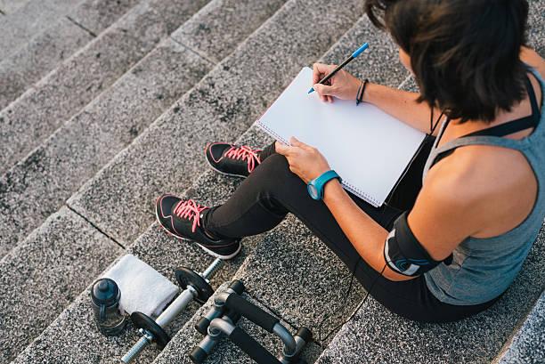 메모장에 글을 쓰는 그녀의 목표에 초점을 맞춘 도시 여성 운동 선수 - 일과 뉴스 사진 이미지