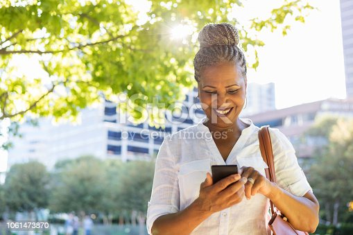 istock Urban female executive checks her messages on her smartphone 1061473870