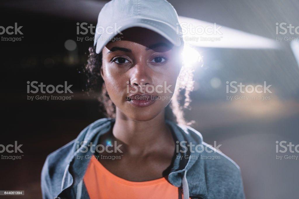 Urban female runner in city at night stock photo