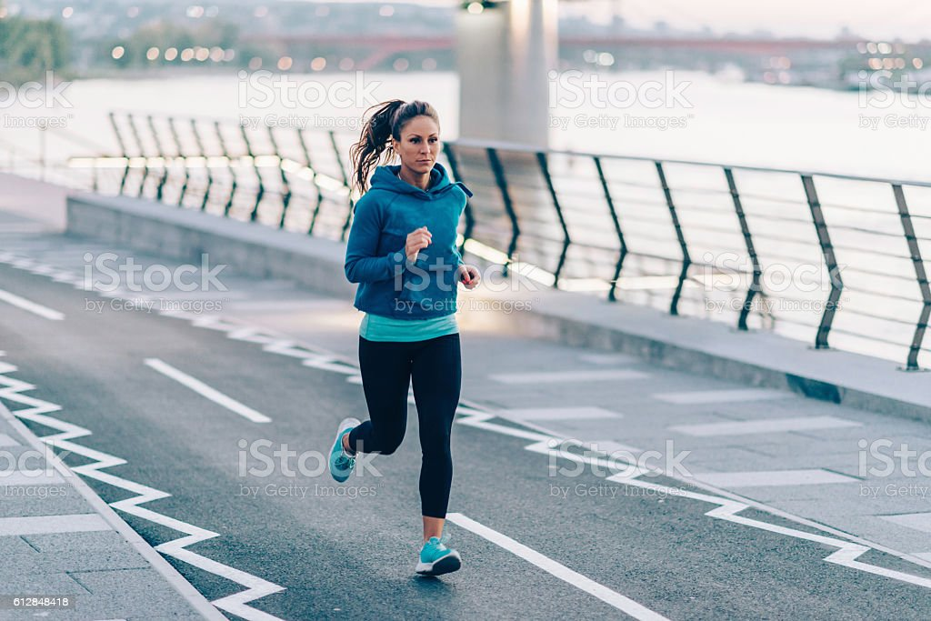 Urban fitness. Woman running by the river stock photo