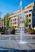 istock Urban fountain in front of modern complex of apartment buildings, Warsaw, Poland 1093304058