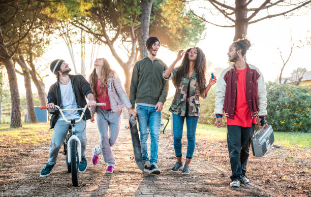 Urban friends gang walking in city skatepark on sunset backlight - Youth and millenial friendship concept with multiracial young people having fun together outdoors - Warm vivid contrast filter stock photo
