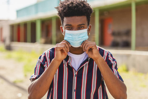 Urban Generation Z Male Outdoors Wearing Face Mask During Pandemic Virus Outbreak stock photo