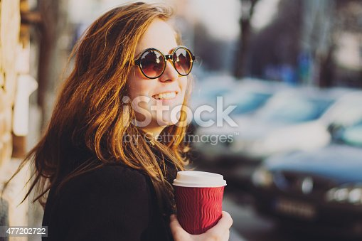 531098549 istock photo Urban girl holding coffee to go 477202722