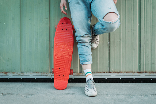 Young woman with a red skateboard, wearing ripped jeans and sneakers leaning on the garage door in the city neighborhood street