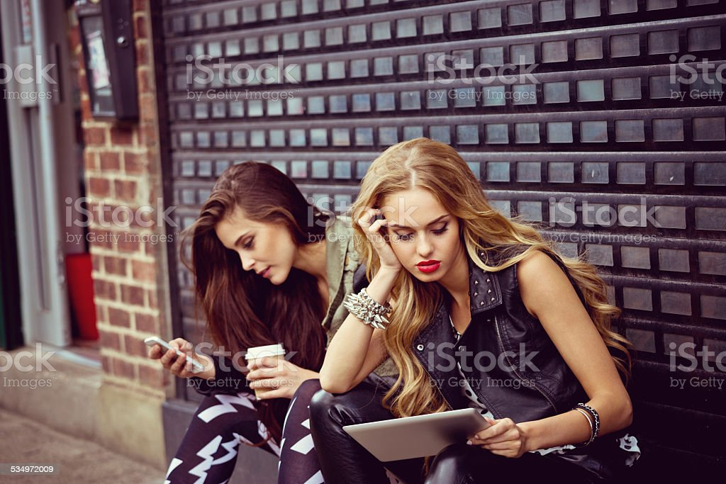 Urban Girls using smart phone and digital tablet Two young women sitting on the city street, drinking take away coffe and using smart phone and digital tablet. 20-24 Years Stock Photo