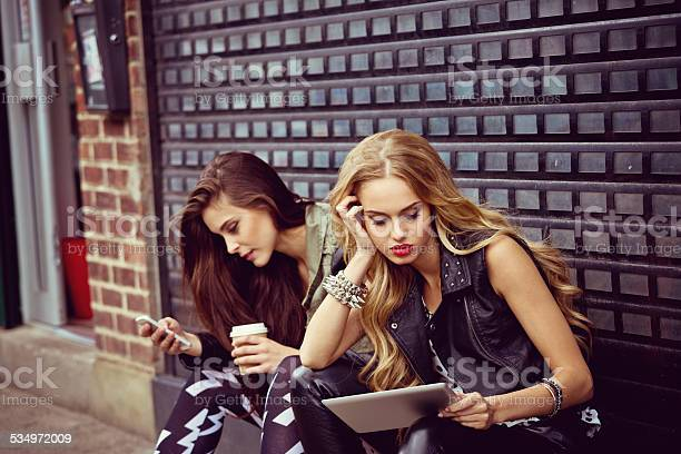 Urban Girls Using Smart Phone And Digital Tablet Stock Photo - Download Image Now