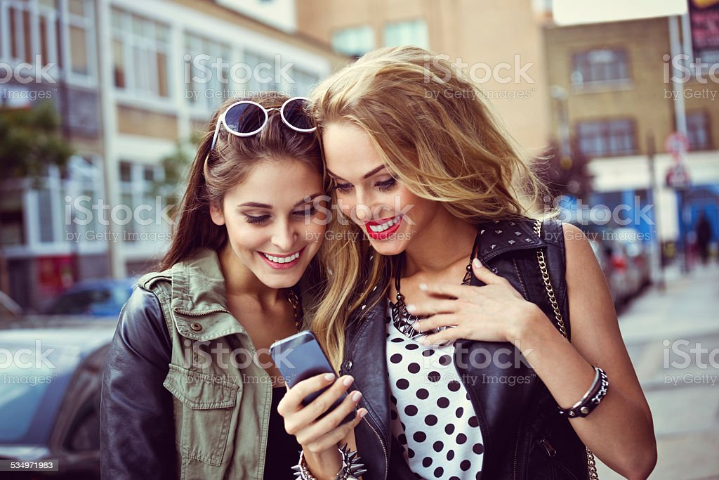 Urban girls using smart phone on the street Two happy friends standing on the street and using smart phone.  20-24 Years Stock Photo