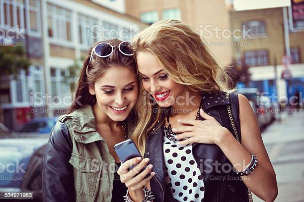 Urban Girls Using Smart Phone On The Street Stock Photo - Download Image Now