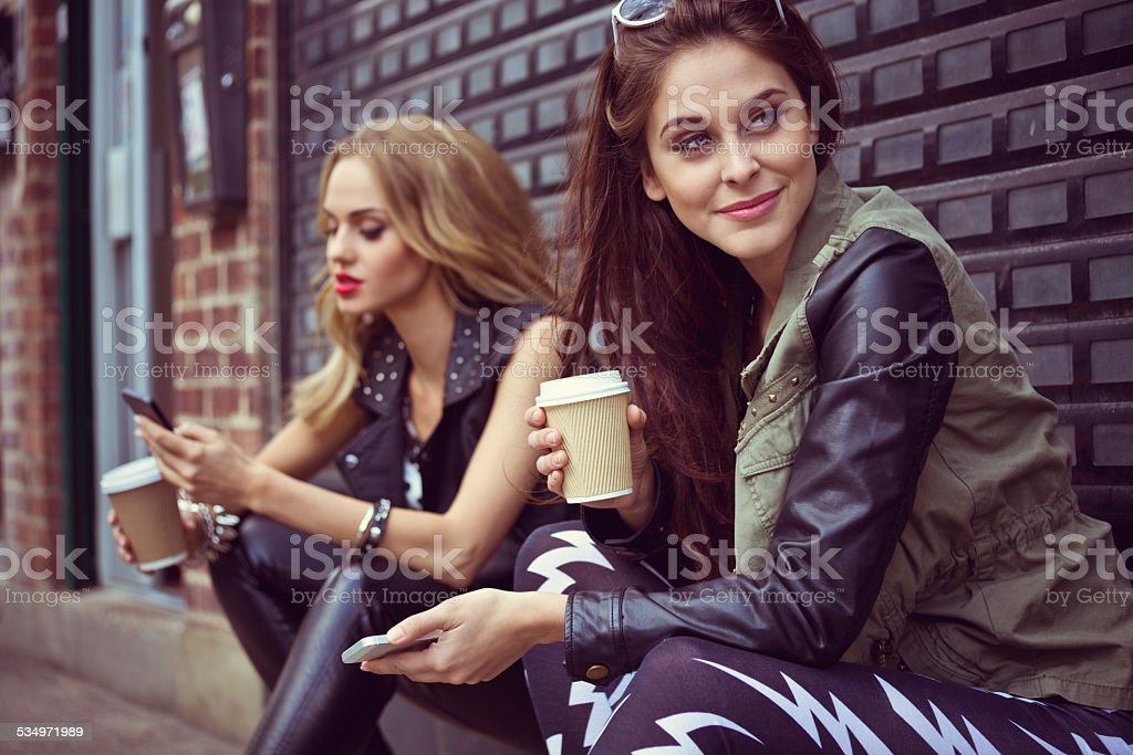 Urban Girls using smart phones Two young women sitting on the city street, drinking take away coffe and using smart phones. Focus on beautiful brunette. 20-24 Years Stock Photo