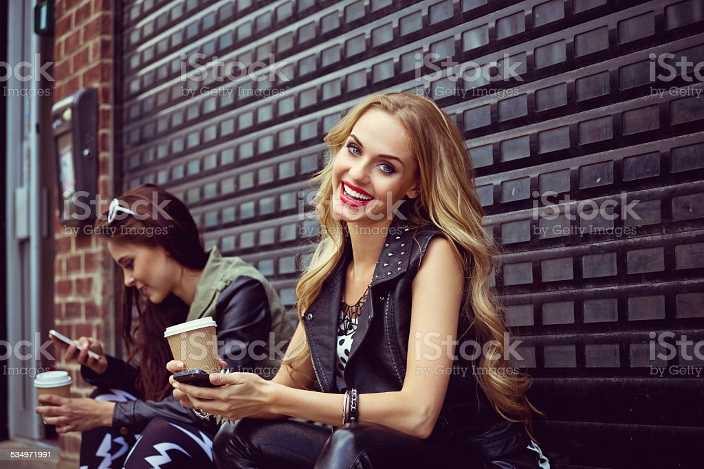Urban Girls using smart phones Two young women sitting on the city street, drinking take away coffe and using smart phones. Blonde woman smiling at the camera. 20-24 Years Stock Photo