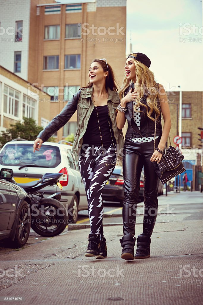 Urban girls walking down the street Two happy friends wearing rock and roll style clothes walking down the street. 16-17 Years Stock Photo
