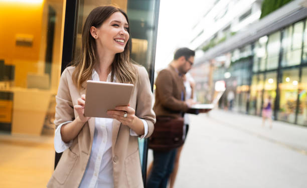 Urban happy business woman using tablet computer and working stock photo