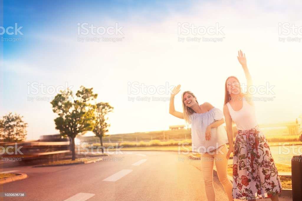 Urban hipster girls hitchhiking on roadside stock photo