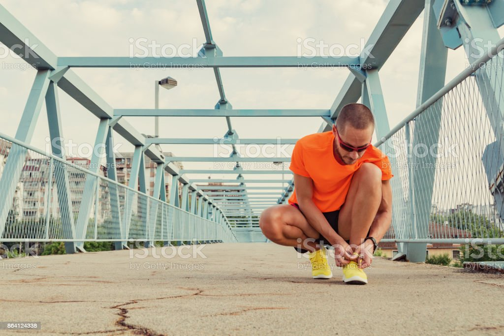 Urban jogger tying running shoes on the asphalt. royalty-free stock photo