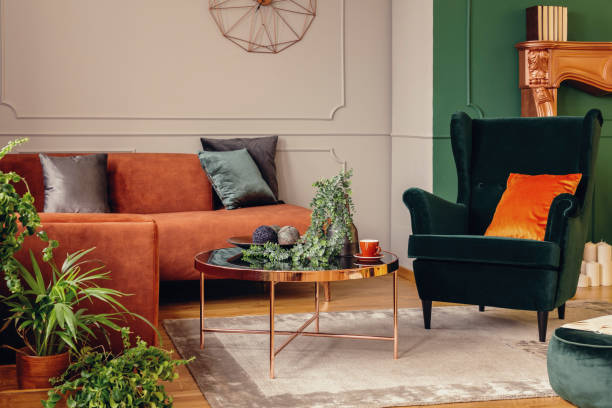 Urban jungle in beautiful living room with grey, orange and green interior stock photo