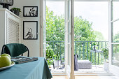 Urban jungle with green plants and trees outside a white dining room interior with place to rest on a beautiful and modern balcony