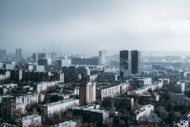 Urban landscape during the storm Megapolis cityscape from a high point during heavy rain: residential district in the foreground, low dark thunderclouds, rain in a hazy distance, office business skyscrapers in the middle urban sprawl stock pictures, royalty-free photos & images