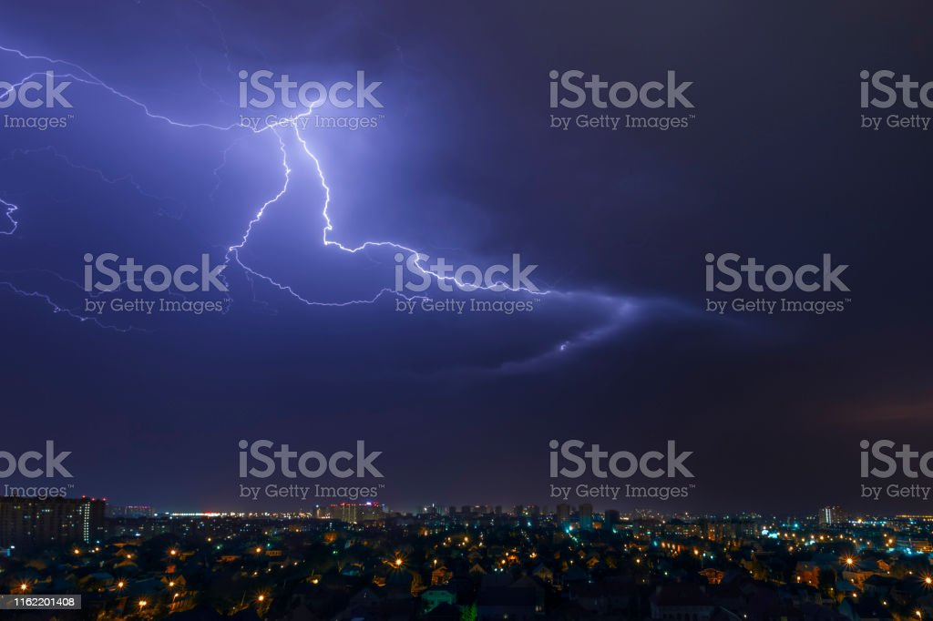 urban landscape, thunderstorm and lightning across the sky over the...