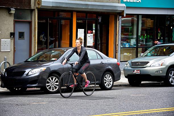 urban life, new york city, female bicyclist passing vehicles, brooklyn - telelens stockfoto's en -beelden