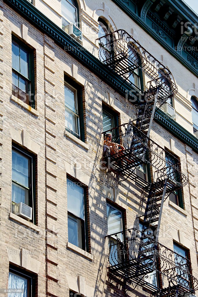 Urban Life, New York City, Woman on Fire Escape, Manhattan stock photo
